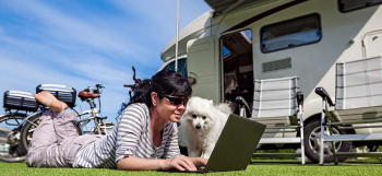 Woman-watching-tv-on-her-laptop-by-her-motorhome.jpg